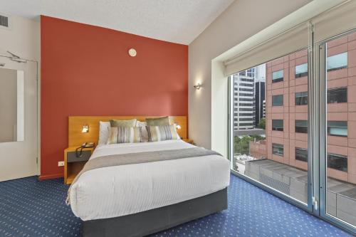 A bed or beds in a room at Melbourne Hotel CBD