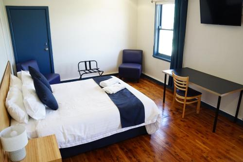 A bed or beds in a room at Gunnedah Hotel