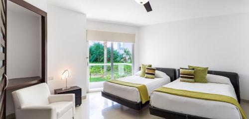 Кровать или кровати в номере Mareazul Beach Front Resort Playa del Carmen