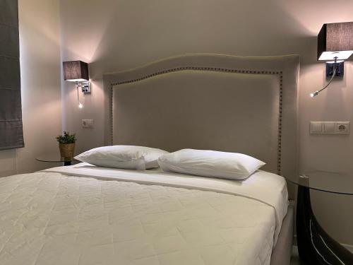 A bed or beds in a room at 24K Athena Suites