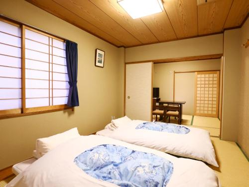 A bed or beds in a room at Ryokan Kamogawa Asakusa