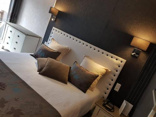 A bed or beds in a room at Le Trophée By M Hôtel Spa