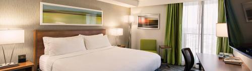 A bed or beds in a room at Holiday Inn Winnipeg - Airport West