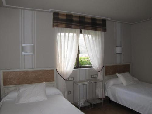 A bed or beds in a room at Hotel Migal