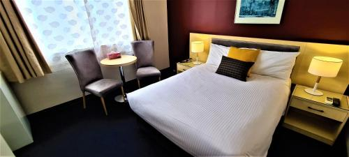 A bed or beds in a room at Brunswick Tower Hotel