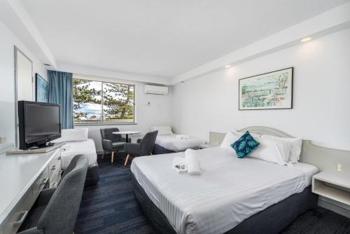 A bed or beds in a room at Alloggio Newcastle Beach