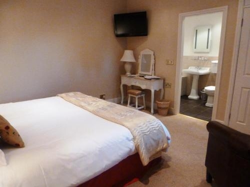 A bed or beds in a room at Blackaddie House Hotel