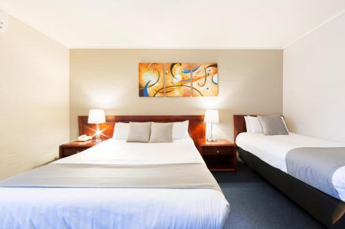 A bed or beds in a room at ibis Styles Canberra