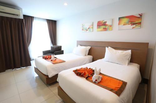 A bed or beds in a room at Crystal Suites Suvarnbhumi Airport