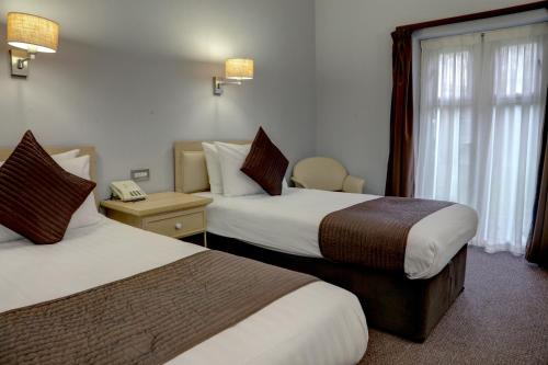 A bed or beds in a room at The Regency Hotel; Sure Hotel Collection by Best Western