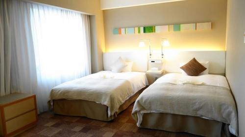 A bed or beds in a room at City Plaza Osaka