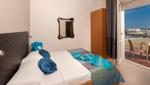 A bed or beds in a room at G House Rimini Spiaggia