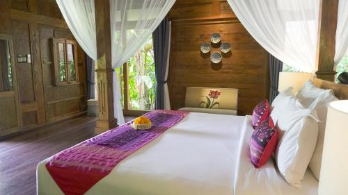 A bed or beds in a room at Ubud Valley Boutique Resort
