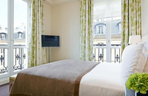 A bed or beds in a room at Grand Hôtel Du Palais Royal