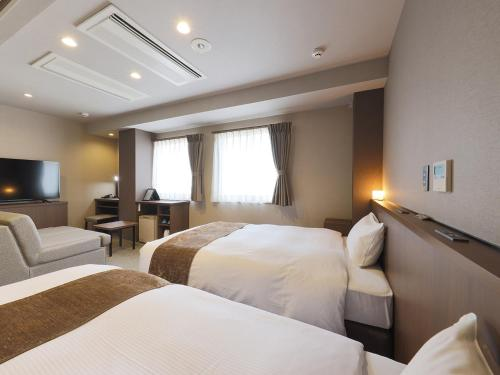 A bed or beds in a room at Matsue Urban Hotel