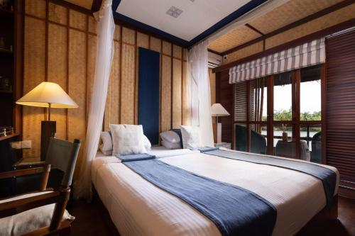 A bed or beds in a room at Yathra Houseboat by Jetwing