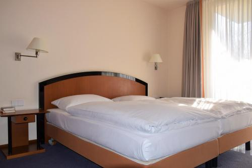A bed or beds in a room at City Hotel Dresden Radebeul