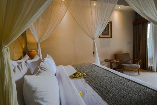 A bed or beds in a room at Purana Suite Ubud