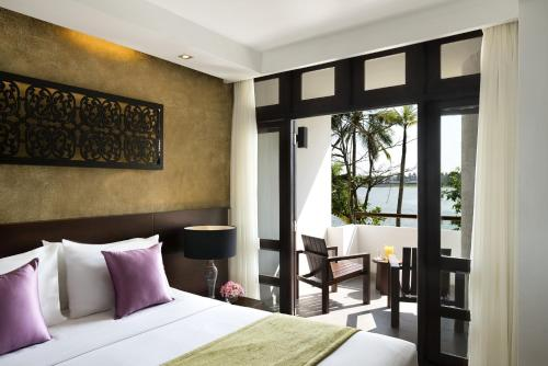 A bed or beds in a room at Avani Kalutara Resort