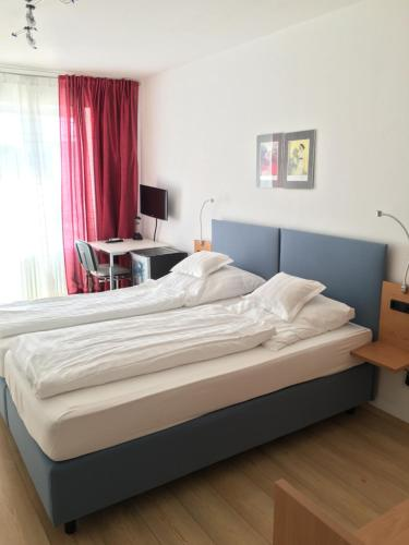 A bed or beds in a room at Hotel Bairischer Hof
