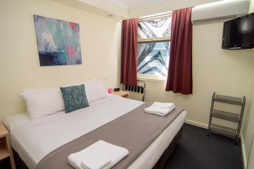 A bed or beds in a room at Miami Hotel Melbourne