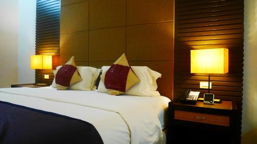 A bed or beds in a room at Circle Inn Hotel and Suites Bacolod