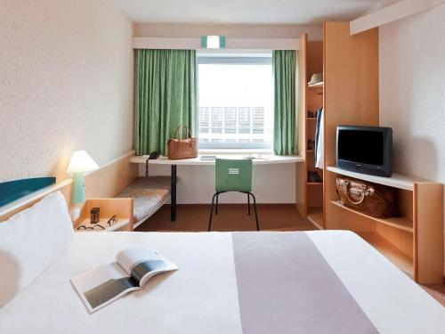 A television and/or entertainment center at Ibis Madrid Alcorcon Tresaguas