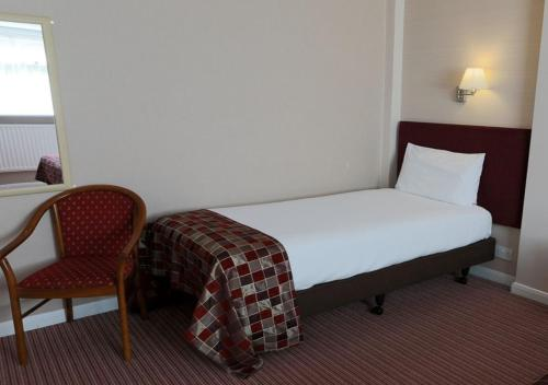A bed or beds in a room at King Charles Hotel