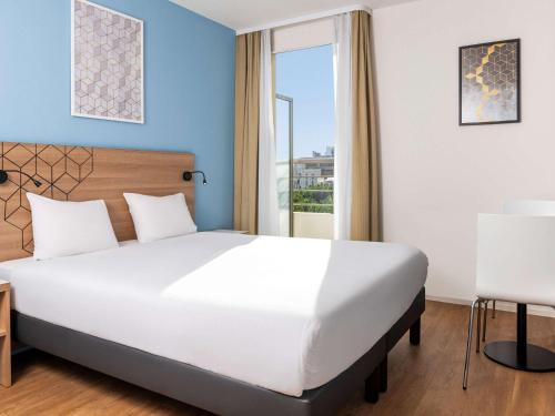 A bed or beds in a room at Aparthotel Adagio Access Paris Quai d'Ivry