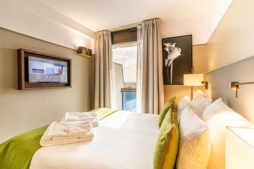 سرير أو أسرّة في غرفة في أجنحة فريزر أرموني باريس لا ديفانس