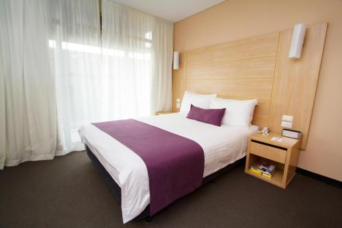 A bed or beds in a room at Sage Hotel Adelaide