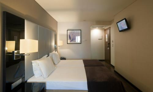 A bed or beds in a room at TURIM Luxe Hotel
