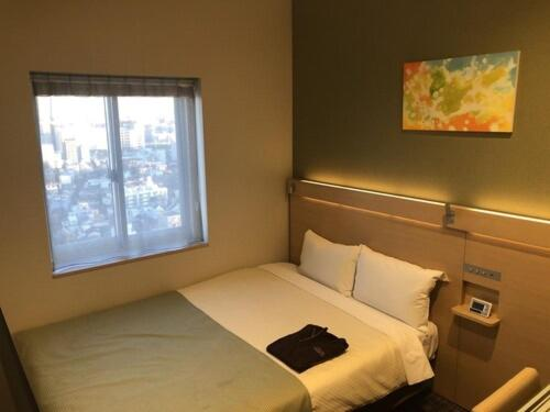 A bed or beds in a room at Ours Inn Hankyu