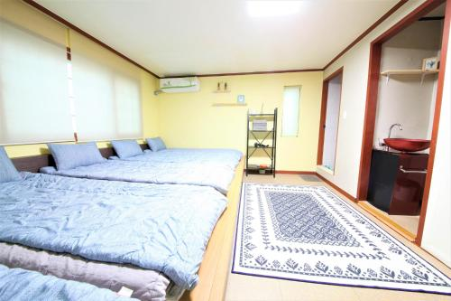 A bed or beds in a room at Twin Panda Guesthouse