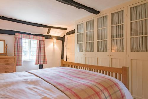 A bed or beds in a room at Walnut Tree Cottage