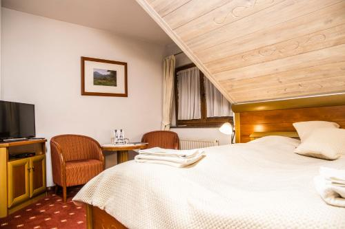 A bed or beds in a room at Hotel Promyk Wellness & Spa