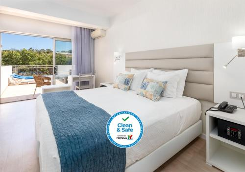 A bed or beds in a room at Carvi Beach Hotel
