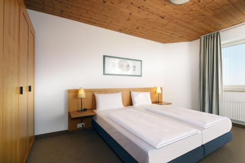 A bed or beds in a room at Dorint Resort Winterberg Sauerland