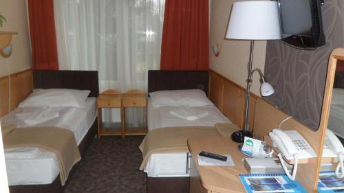 A bed or beds in a room at Nereus Park Hotel