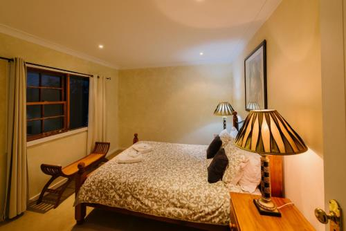 A bed or beds in a room at Barrington Hideaway- River Cottages