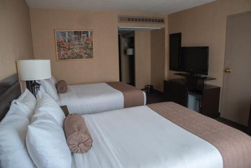 A bed or beds in a room at Ramada Plaza by Wyndham Calgary Downtown
