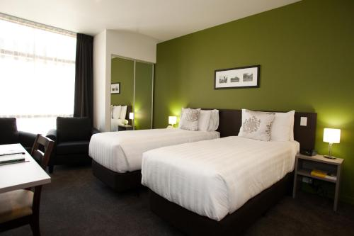 A bed or beds in a room at Quest Rotorua Central