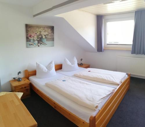 """Ein Bett oder Betten in einem Zimmer der Unterkunft Pension """"Dorfkrug"""""""