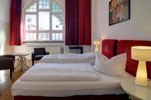 A bed or beds in a room at Alte Lohnhalle Kultur- und Tagungshotel