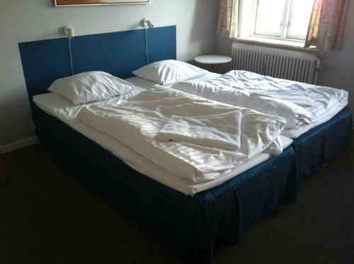A bed or beds in a room at Det Lille Hotel