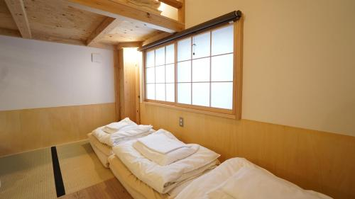 A bed or beds in a room at Poly Hostel 2 Namba