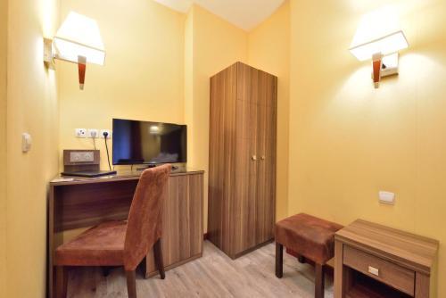 Una televisión o centro de entretenimiento en Hotel Capitole