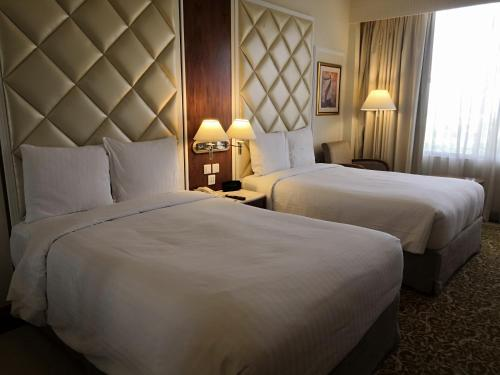 A bed or beds in a room at Islamabad Marriott Hotel