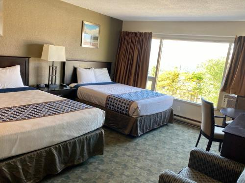 A bed or beds in a room at Knights Inn Kamloops