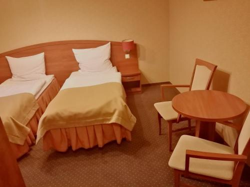 A bed or beds in a room at Hotel Borowianka